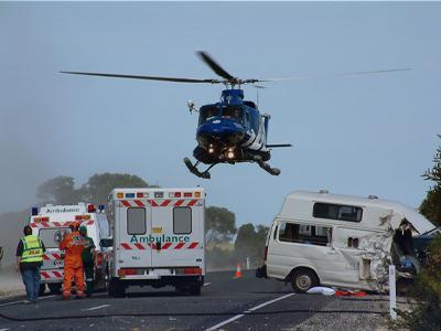 helicopter flying above ambulance car crash scene