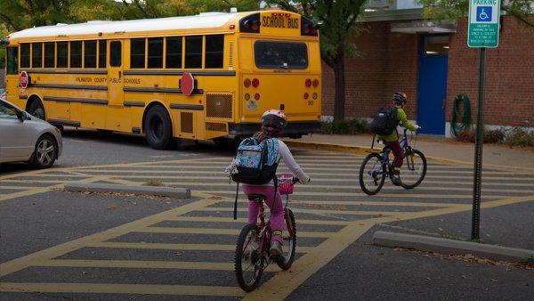 kids on crosswalk with school bus in background