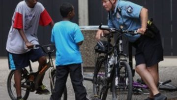 school officer on bicycle talking to kids