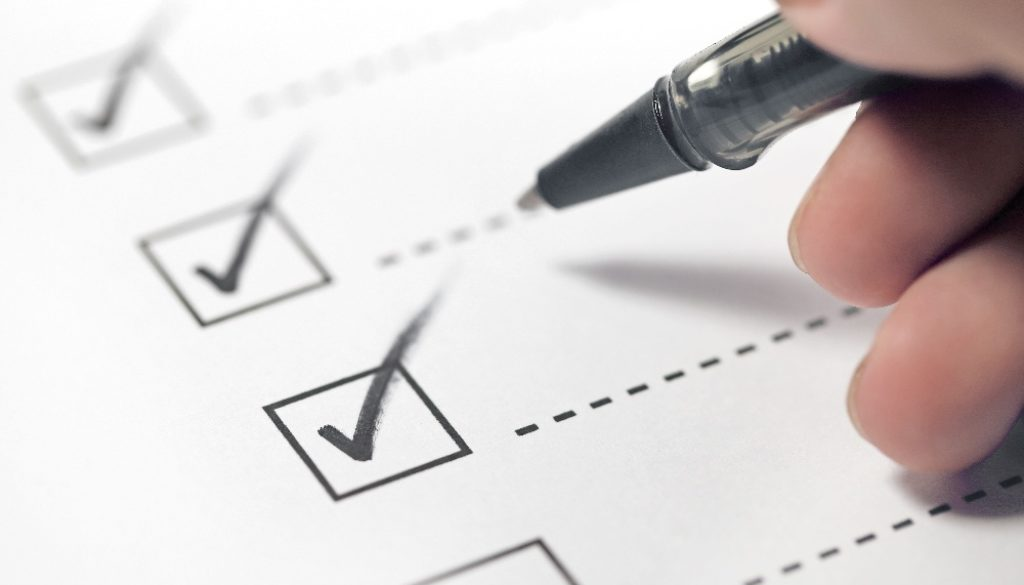 checklist with pen checking off items