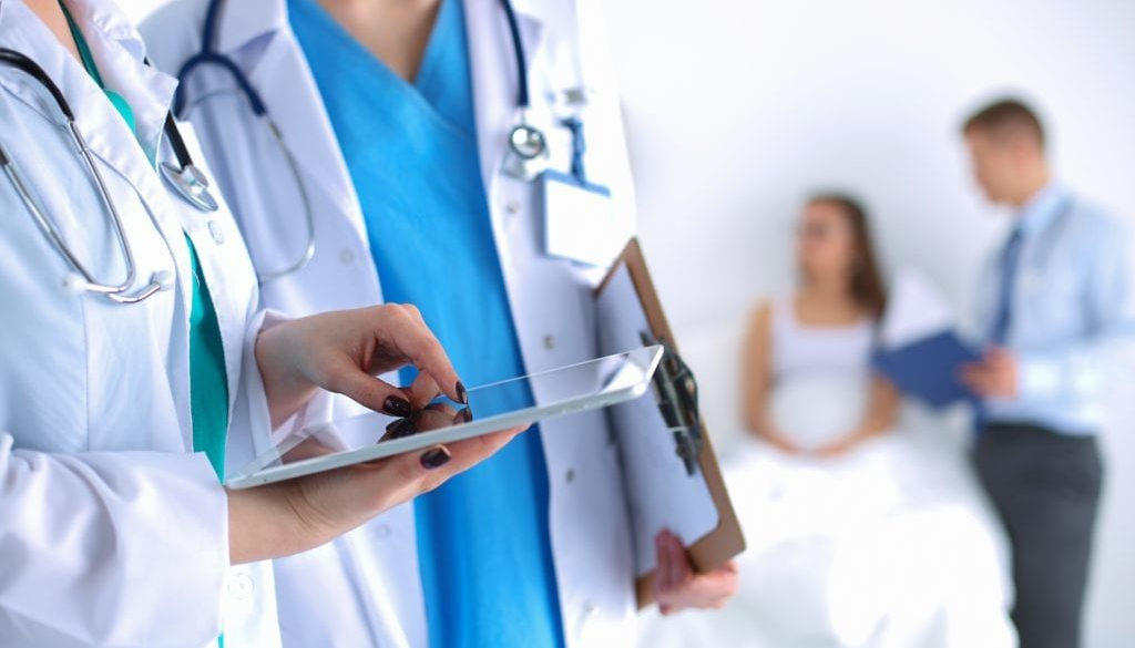 doctor and nurse talking holding tablet with patients in background