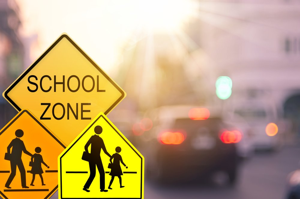 school crosswalk signs with traffic in background