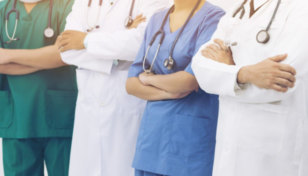 nurses standing with arms crossed in scrubs