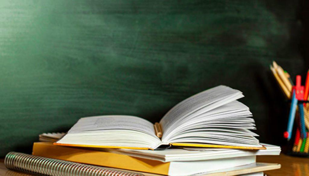 open text book on desk in front of blackboard