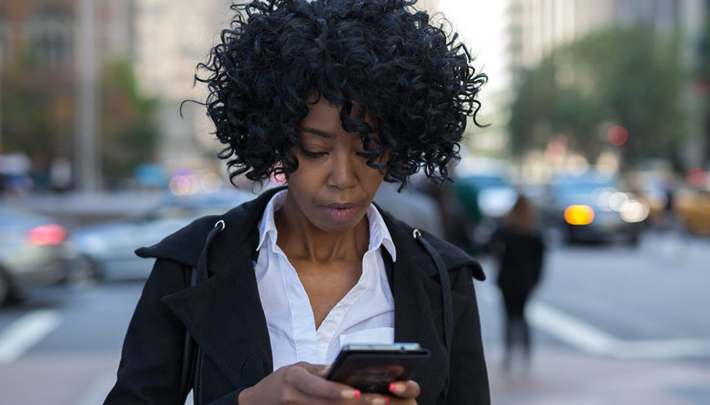 Business woman in New York City texting on cell phone