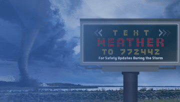 tornado touching down with billboard displaying weather alert opt in phone number