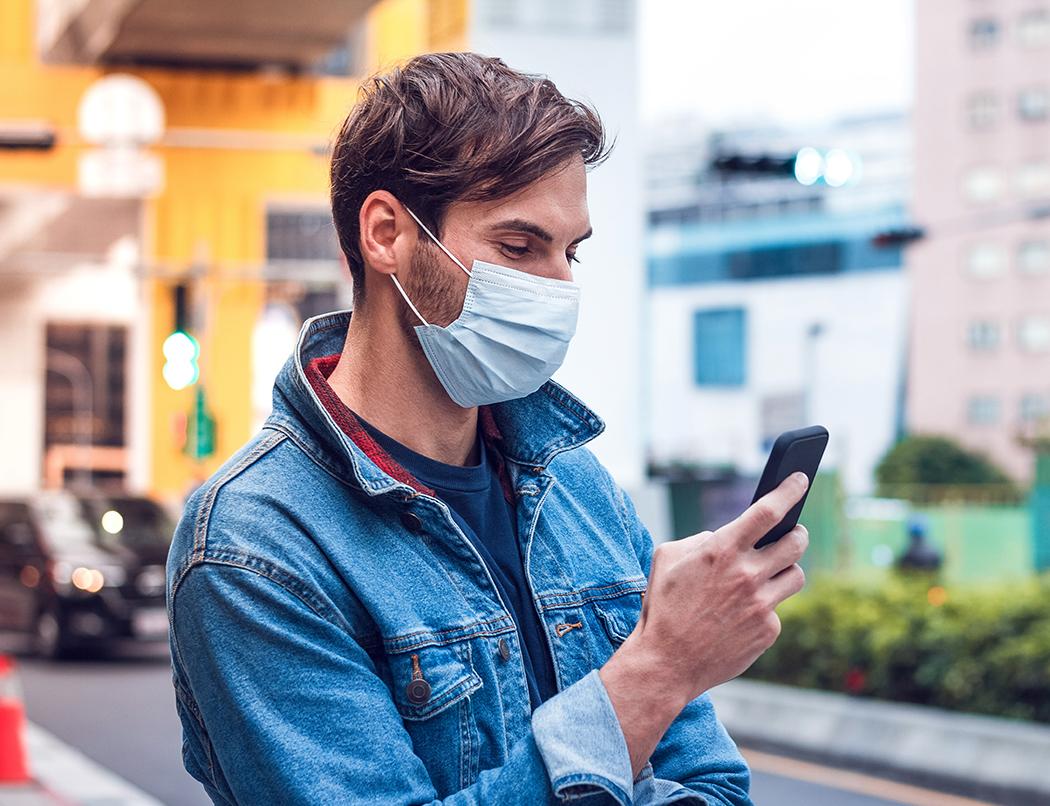 man on phone outside wearing mask