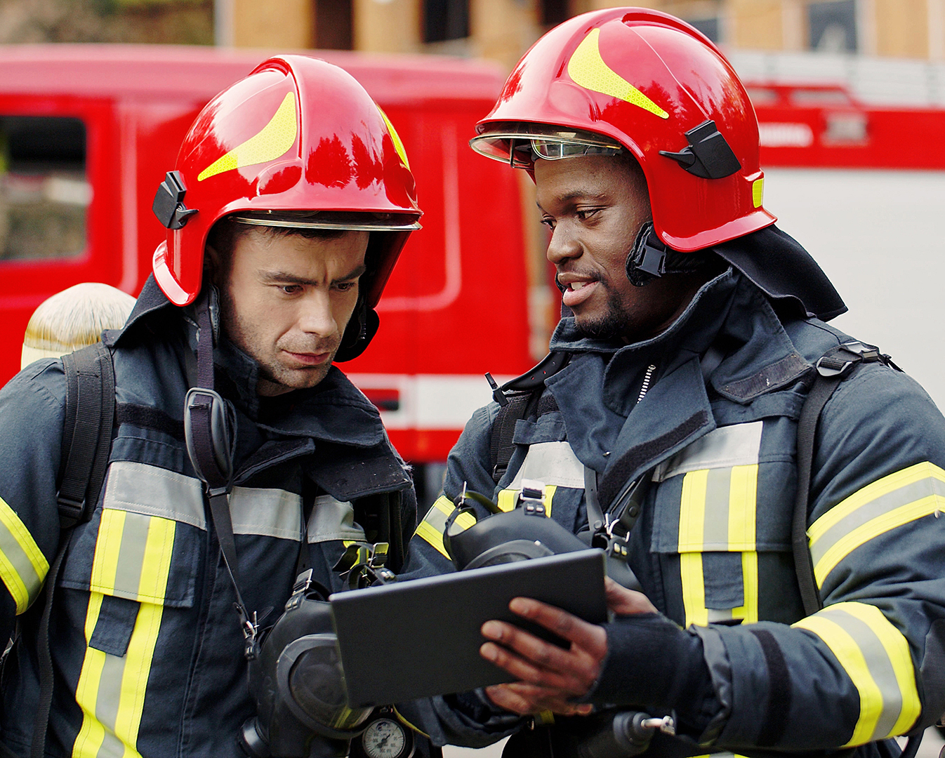 firefighters looking at tablet in uniform at scene of incident