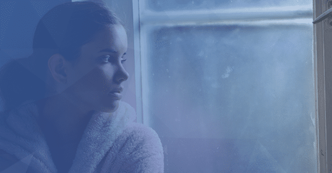 woman looking out window solemn mental health blue overlay background