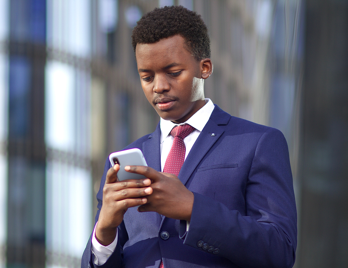 business man looking at phone outside
